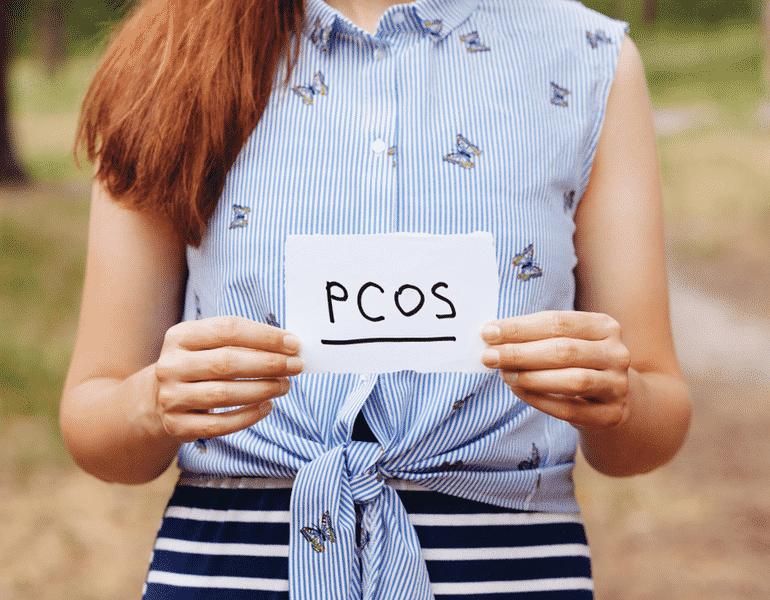 Woman holding a piece of paper with PCOS diagnosis
